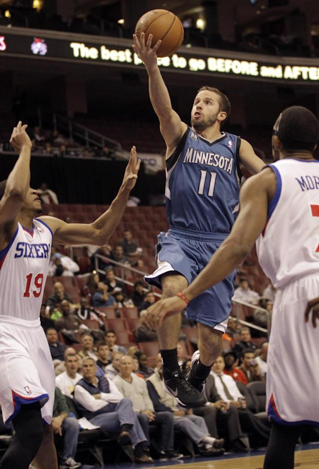 Minnesota Timberwolves' Jose Barea, center, drives to the basket past Philadelphia 76ers' Rodney Williams, left, and Darius Morris in the first half of a preseason NBA basketball game, Wednesday, Oct. 23, 2013, in Philadelphia. (AP Photo/Laurence Kesterson)