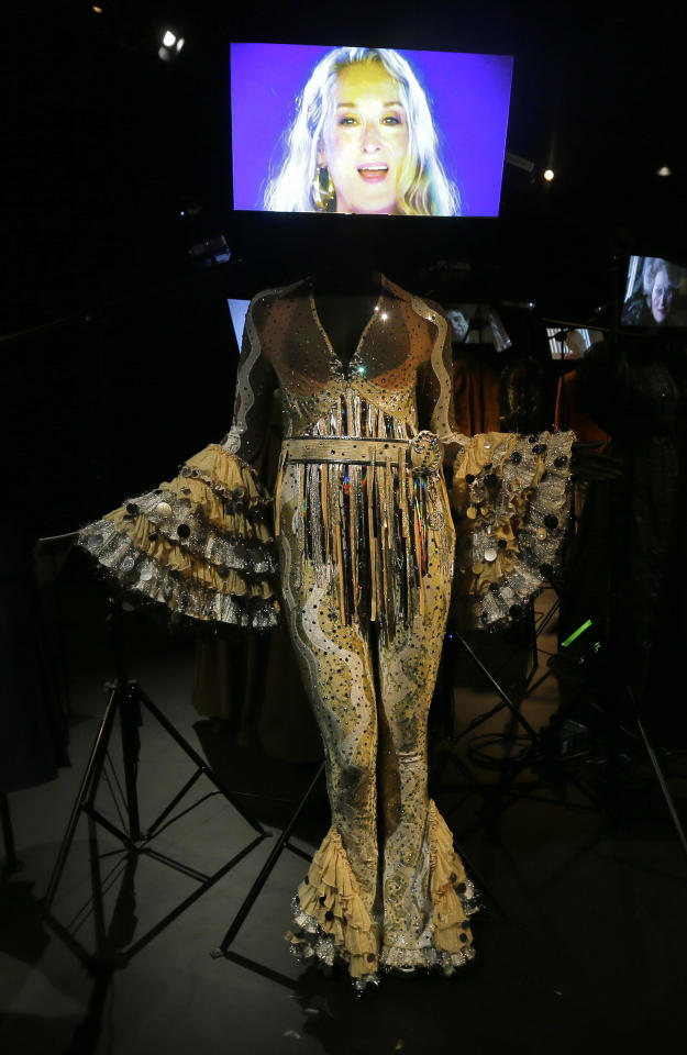 A costume designed by Ann Roth and used in the 2008 film Mamma Mia for the character Donna played by Meryl Streep is seen on display at the Hollywood Costume exhibition at the Victoria and Albert museum in London, Tuesday, Oct. 16, 2012. Streep is seen in the video display above the costume.  The show at the Victoria and Albert Museum showcases more than one hundred movie costumes from a century of film-making. The exhibition opens to the public on Oct. 20, 2012 and run till 27 Jan. 2013. (AP Photo/Alastair Grant)