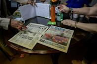 Hispanic cleaners from Ground Zero look at old newspapers that reported the death of Rafael Hernandez, an undocumented Mexican ex-firefighter who co-founded the support group Fronteras de Esperanza (AFP/Ed JONES)