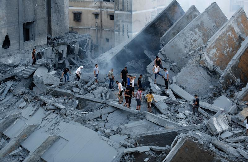 Palestinians inspect the remains of a building destroyed by an Israeli air strike in Gaza City on August 26, 2014 (AFP Photo/Mohammed Abed)