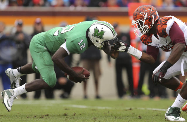 Marshall's Rakeem Cato, left, has his face mask grabbed by Virginia Techs' Dadi Nicholas during the first half of an NCAA college football game Saturday, Sept. 21 2013, in Blacksburg Va. (AP Photo/The Roanoke Times, )