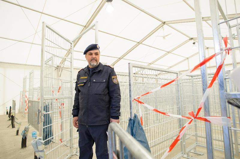 An Austrian police officer works at an empty refugee centre in Spielfeld at the Austrian-Slovenian border as Austria imposes a new daily migrant limit on February 19, 2016