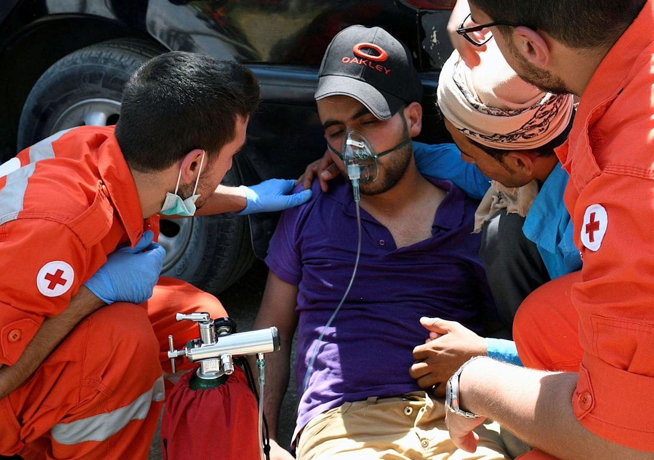 <p>A man is treated for smoke inhalation by Red Cross members after a fire tore through a camp for Syrian refugees, near the town of Qab Elias, in Lebanon's Bekaa Valley, July 2, 2017. (Hassan Abdallah/Reuters) </p>