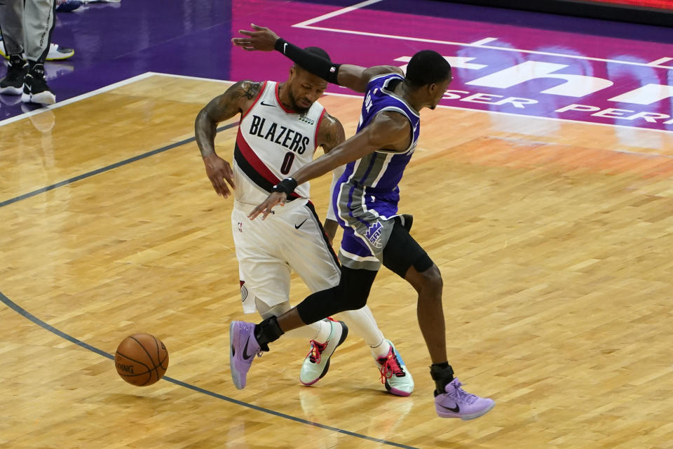 Portland Trail Blazers guard Damian Lillard, left, dodges Sacramento Kings guard De'Aaron Fox, right, during the second quarter of an NBA basketball game in Sacramento, Calif., Wednesday, Jan. 13, 2021. (AP Photo/Rich Pedroncelli)