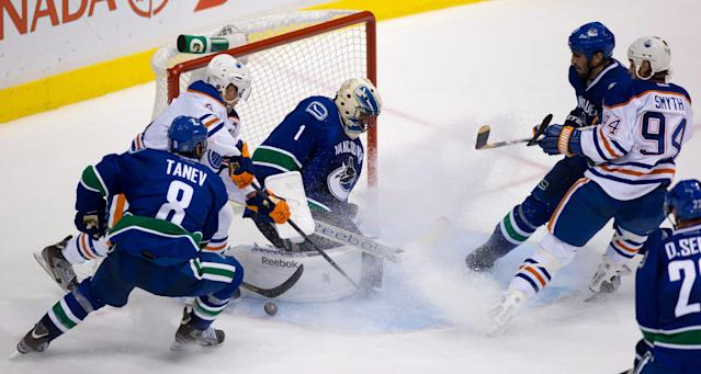 Vancouver Canucks goalie Roberto Luongo, center, stops Edmonton Oilers' Taylor Hall, second from left, as Canucks' Chris Tanev, left, and Jason Garrison and Oilers' Ryan Smyth, right, watch during the second period of a preseason NHL hockey game Wednesday, Sept. 18, 2013, in Vancouver, British Columbia. (AP Photo/The Canadian Press, Darry Dyck)
