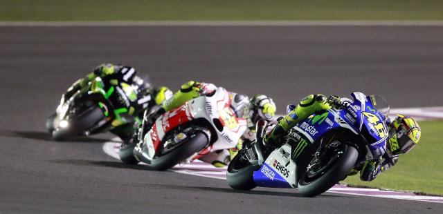 Yamaha MotoGP rider Valentino Rossi (R) of Italy races during a free practice session at the MotoGP World Championship at the Losail International circuit in Doha March 22, 2014. REUTERS/ Mohammed Dabbous (QATAR - Tags: SPORT MOTORSPORT)