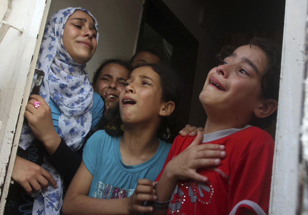 Palestinian children mourn for militant Basil Ahmad during his funeral in Bureij refugee camp, central Gaza Strip, Friday, June 22, 2012. Palestinian sources say that Ahmad was killed during an Israeli airstrike east of Bureij refugee camp on Friday. An Israeli airstrike killed a Gaza militant Friday as he was preparing to launch rockets, Israel's military said, the latest casualty in a week-long exchange of cross-border attacks. (AP Photo/Ashraf Amra)