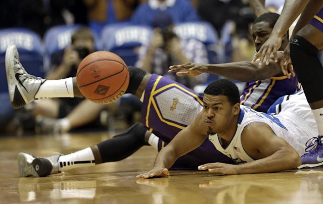 Duke's Quinn Cook and East Carolina's Caleb White, rear, fall to the floor in pursuit of the ball during the first half of an NCAA college basketball game in Durham, N.C., Tuesday, Nov. 19, 2013. (AP Photo/Gerry Broome)