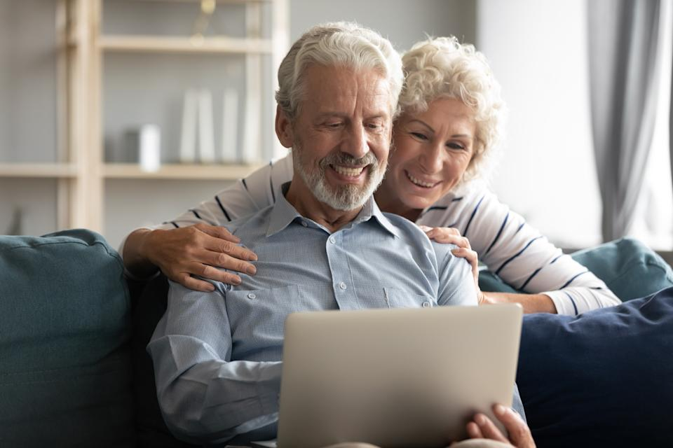 60s-70s couple plan vacation use pc, browse booking website, learn hotel or ticket options online, wife hugs from behind husband family enjoy virtual entertainment new apps, reading last positive news