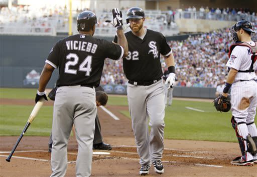 Chicago White Sox's Adam Dunn (32) is congratulated by Dayan Viciedo (24) after hitting a solo home run against Minnesota Twins starting pitcher Kevin Correia during the second inning of a baseball game, Tuesday, May 14, 2013, in Minneapolis. (AP Photo/Genevieve Ross)