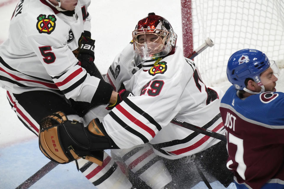 Chicago Blackhawks defenseman Connor Murphy, left, crashes into goaltender Marc-Andre Fleury after getting called for holding Colorado Avalanche left wing Tyson Jost on a breakaway shot during the second period of an NHL hockey game Wednesday, Oct. 13, 2021, in Denver. (AP Photo/David Zalubowski)