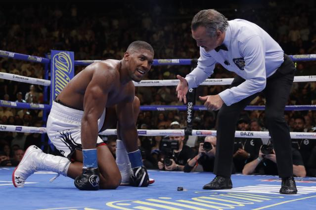 FILE - In this Saturday, June 1 , 2019 file photo, Britain's Anthony Joshua reacts as the referee counts for him after he was knocked down during the seventh round of a heavyweight title boxing match against Mexican American boxer Andy Ruiz, in New York. Joshua is starting all over as he prepares for his rematch against Andy Ruiz Jr. for the world heavyweight titles. Joshua has had to reinvent himself after losing his IBF, WBA and WBO belts to the Mexican in June in one of boxing's biggest shocks. (AP Photo/Frank Franklin II, File)