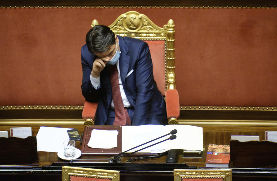 FILE - In this Wednesday, Dec. 9, 2020 file photo, Italian Premier Giuseppe Conte touches his forehead as he takes a break while addressing the Senate in Rome. When Giuseppe Conte exited the premier's office, palace employees warmly applauded in him appreciation. But that's hardly likely to be Conte's last hurrah in politics. Just a few hours after the handover-ceremony to transfer power to Mario Draghi, the former European Central Bank chief now tasked with leading Italy in the pandemic, Conte dashed off a thank-you note to citizens that sounded more like an ''arrivederci″ (see you again) then a retreat from the political world he was unexpectedly propelled into in 2018.(Mauro Scrobogna/LaPresse via AP)