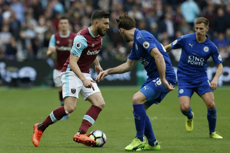 West Ham United's midfielder Robert Snodgrass (L) vies with Leicester City's defender Christian Fuchs during the English Premier League football match March 18, 2017