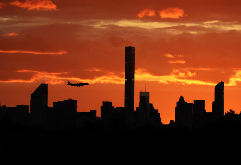 FILE - In this Sept. 6, 2016, file photo, a plane flies near the Manhattan skyline at sunset in New York. The latest mass shootings in the United States have triggered multiple countries to warn their citizens to be wary of travel conditions there. (AP Photo/Darron Cummings, File)