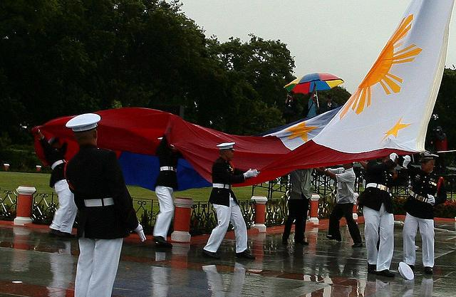 Honor guards struggle against the rain and wind as they raise an already wet giant Philippine flag to start the celebrations for national hero Jose Rizal's 150th birthday, held at the Rizal Shrine in Luneta Park, Manila. (Mike Alquinto/NPPA Images)