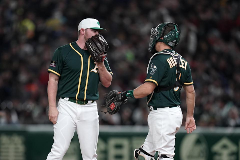 TOKYO, JAPAN - MARCH 17: Pitcher Liam Hendriks #16 of the Oakland Athletics talks with Catcher Nick Hundley #3 in the bottom of 1st inning during the game between Hokkaido Nippon-Ham Fighters and Oakland Athletics at Tokyo Dome on March 17, 2019 in Tokyo, Japan. (Photo by Masterpress/Getty Images)
