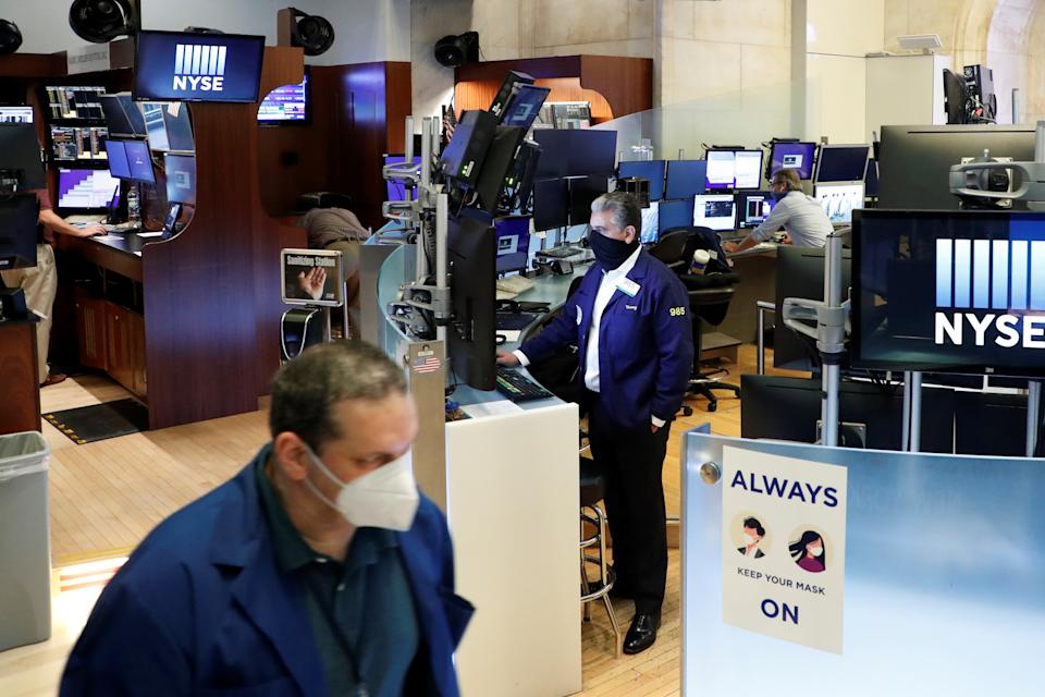 Traders with masks work on the first day of in-person trading since the closure during the outbreak of the coronavirus disease (COVID-19) on the floor at the New York Stock Exchange (NYSE) in New York, U.S., May 26, 2020. REUTERS/Brendan McDermid