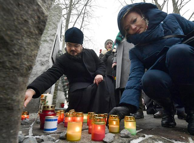 <p>Members of the Minsk, Belarus Jewish community light candles at the Minsk Ghetto Victims Memorial in a former Jewish cemetery on the eve of Holocaust Memorial Day, Jan. 26, 2018. (Photo: Viktor Drachev/TASS via Getty Images) </p>