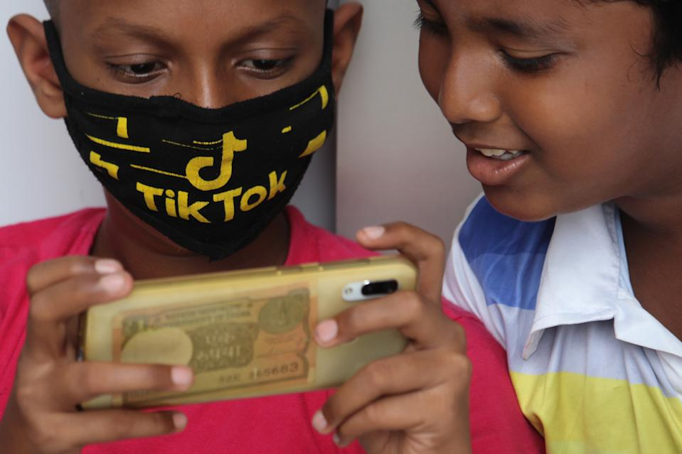 A boy wearing a face mask with the TikTok logo uses a mobile phone outside the downed shutters of a shop in Mumbai, India on July 29, 2020. Photo: Himanshu Bhatt/NurPhoto/Getty