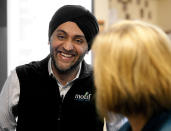 In this March 18, 2014 photo Motif Investing founder Hardeep Walia talks with staff at Oak Grove Middle School in Fargo, North Dakota. Sixth grade teacher Dave Carlson started a competition between regular and advance math classes at Oak Grove and registered his students with Motif Investing, a company that enables customers to buy baskets of stocks. In the end, Carlson's regular math class yielded a nearly 22 percent gain and trounced every university club participating in a contest that was held at the same time. (AP Photo/Bruce Crummy)