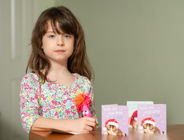 Florence Widdicombe, 6, at her home in Tooting, south London, writing in a Tesco Christmas card from the same pack as a card she found contained a message from a Chinese prisoner. The family who found a message from a Chinese prisoner in a Christmas card said they thought it was a