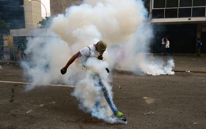 A demonstrator clashes with the police during a rally against Venezuelan President Nicolas Maduro, in Caracas on April 19 - AFP