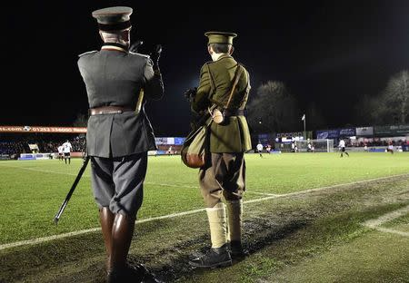 Two men wearing replica World War I British and German army uniforms watch a soccer match between the British Army and German Bundeswehr at Aldershot Town FC stadium in Aldershot in south England, December 17, 2014. REUTERS/Toby Melville