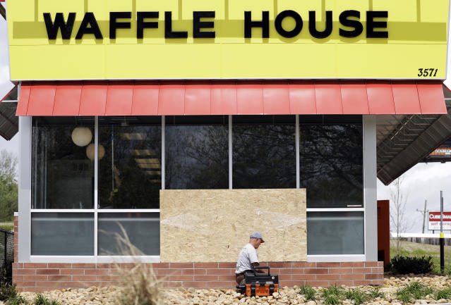 A worker vacuums up shattered glass outside a Waffle House restaurant in Antioch, Tenn., on April 23, 2018. (Photo: Mark Humphrey/AP)
