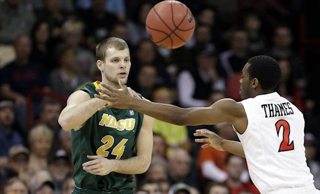 North Dakota State's Ryan Staten (24) passes as San Diego State's Xavier Thames defends in the first half during the third-round of the NCAA men's college basketball tournament in Spokane, Wash., Saturday, March 22, 2014. (AP Photo/Elaine Thompson)