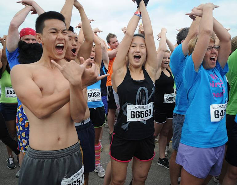 In this June 17, 2012 photo, Koncheng Moua, left, and Christine Moua of Lancaster first time racers, get pumped up to start the Warrior Dash at Pocono Raceway in Long Pond, Pa. Virtually overnight, obstacle courses have become a favorite diversion of thrill-seekers and weekend warriors. (AP Photo/Scranton Times & Tribune, Melissa Evanko) WILKES BARRE TIMES-LEADER OUT; MANDATORY CREDIT