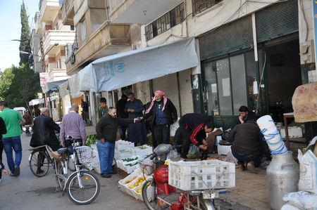 People shop along a street in the city of Homs