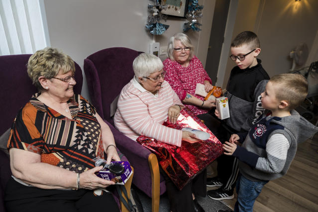 Lewis had been saving his pocket money and wanted to buy presents for pensioners living in the shared housing scheme. Here, Lewis and his brother give present to (from left) Mabel Steveson, Selina Irvine, and Linda Mulholland. (PA)