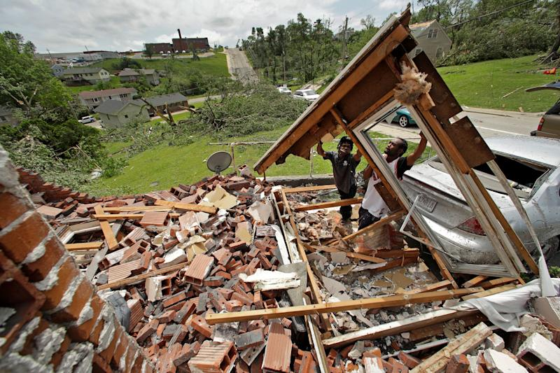 Tavaris McClain, left, and Tyree Thompson clear debris to free McClain's mother's car outside her destroyed home Thursday, May 23, 2019 after a tornado tore though Jefferson City, Mo. late Wednesday. (AP Photo/Charlie Riedel)