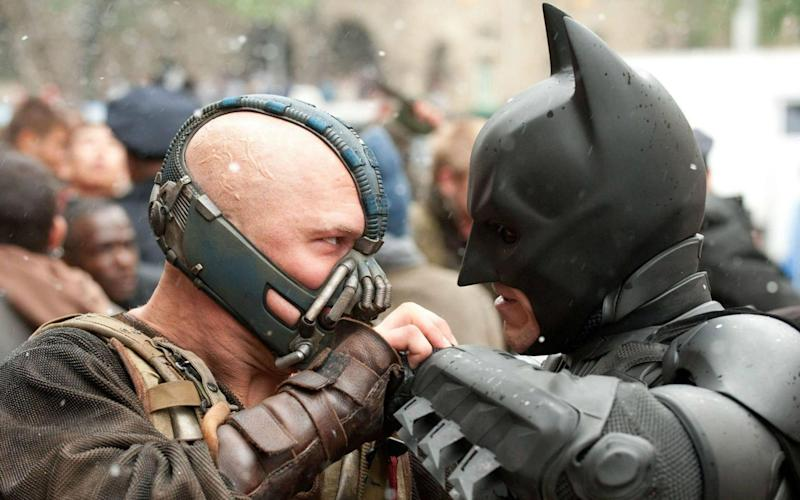 Bane, left, played by Tom Hardy, features in the film 'The Dark Knight Rises' - Credit: REX/Moviestore