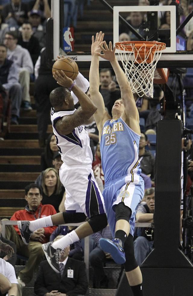 Sacramento Kings guard Marcus Thornton, left, drives to the basket against Denver Nuggets Timofey Mozgov, of Russia, during the first quarter of an NBA basketball game in Sacramento, Calif., Sunday, Jan. 26, 2014. (AP Photo/Rich Pedroncelli)