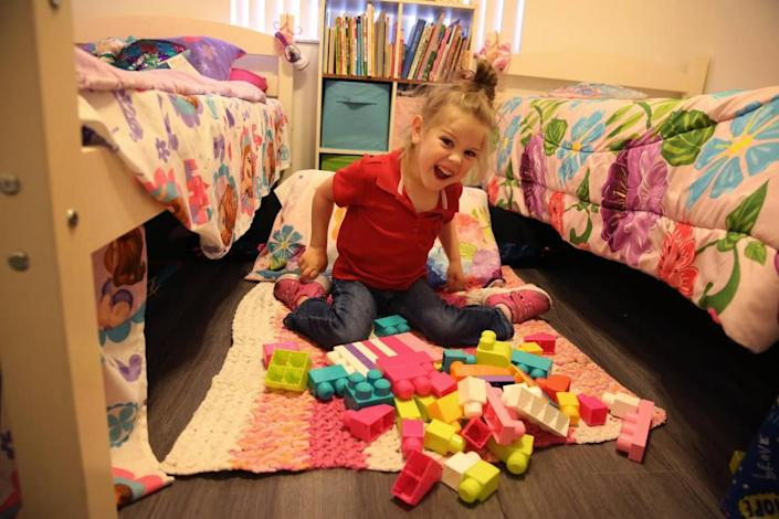 Brooklyn plays with blocks in the bedroom she shares with her sister.