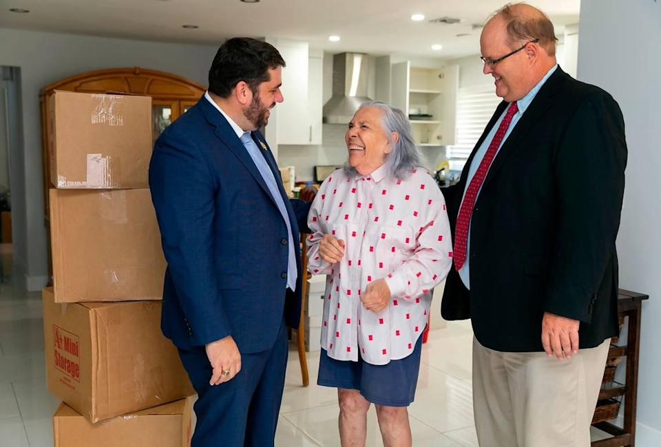 Ana Lazara Rodriguez is photographed alongside her attorneys, Bruce Jacobs, left, and David Winker, inside her new home in Miami's Coral Terrace neighborhood on Monday, Sept. 27, 2021. Rodriguez, who was previously facing eviction, was able to move into this house after an anonymous benefactor bought her the four-bedroom, two-bath home for $690,000.