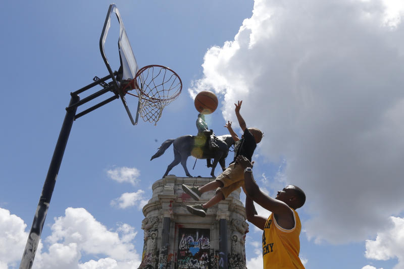 Garth Bowen, lifts his son, Elijah so he can take a shot at a basketball hoop in front of the statue of Confederate General Robert E. Lee on Monument Avenue Sunday, June 21, 2020, in Richmond, Va. A judge extended an injunction delaying the removal of the statue by the state. The statue had become a focal point for the Black Lives Matter movement in Richmond. (AP Photo/Steve Helber)