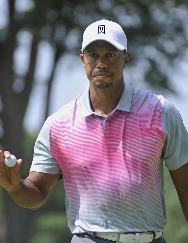 Tiger Woods gives a small wave after a birdie on the second hole, during the first round of the Bridgestone Invitational golf tournament, Thursday, July 31, 2014, in Akron, Ohio. (AP Photo/Phil Long)