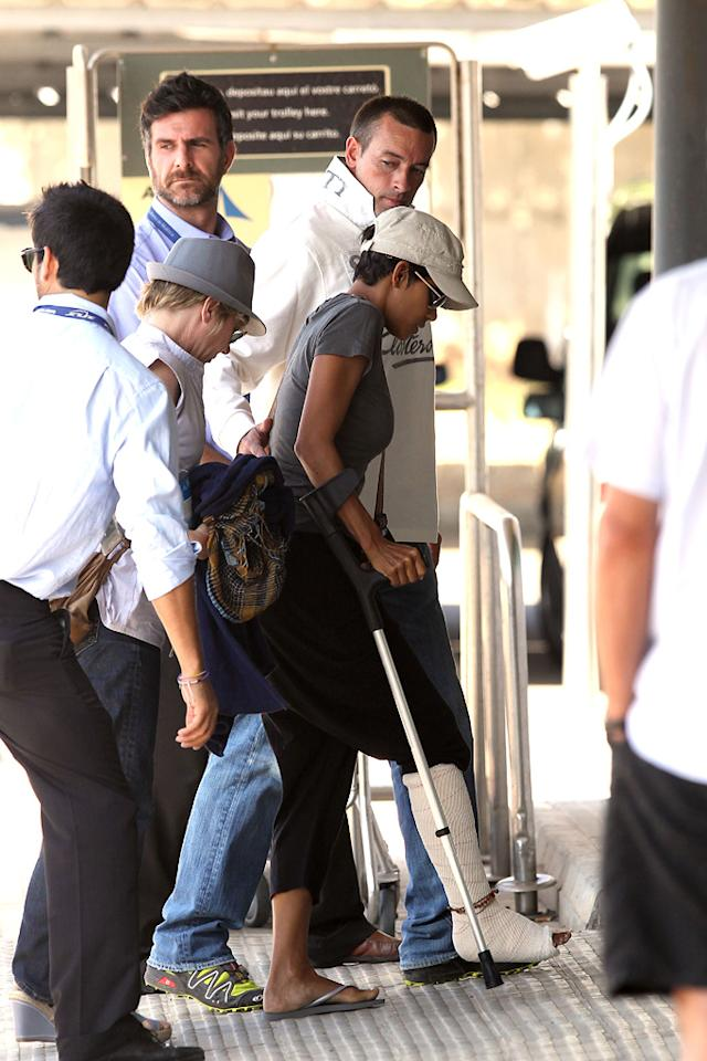 """Oscar winner Halle Berry hobbles out of Spain after breaking her foot on the set of her upcoming film, """"Cloud Atlas,"""" which co-stars Tom Hanks, Hugh Grant, and Susan Sarandon. <a href=""""http://www.infdaily.com"""" target=""""new"""">INFDaily.com</a> - September 22, 2011"""