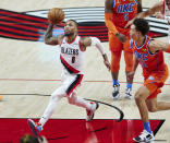Portland Trail Blazers guard Damian Lillard, left, drives to the basket past Oklahoma City Thunder forward Isaiah Roby during the first half of an NBA basketball game in Portland, Ore., Monday, Jan. 25, 2021. (AP Photo/Craig Mitchelldyer)