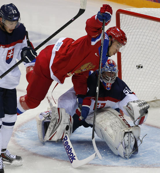 Russia defenseman Alexei Yemelin trips over Slovakia goaltender Jan Laco in the first period of a men's ice hockey game at the 2014 Winter Olympics, Sunday, Feb. 16, 2014, in Sochi, Russia. (AP Photo/Julio Cortez)