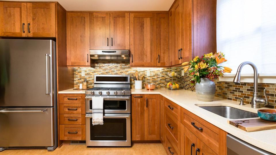 Contemporary upscale home kitchen interior with cherry wood cabinets, quartz countertops, sustainable recycled linoleum floors.