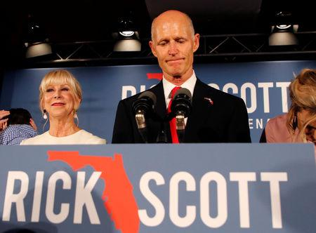 FILE PHOTO: Republican U.S. Senate candidate Rick Scott pauses as he addresses supporters while accompanied by his wife Ann (L) at his midterm election night party in Naples, Florida, U.S. November 6, 2018. REUTERS/Joe Skipper/File Photo
