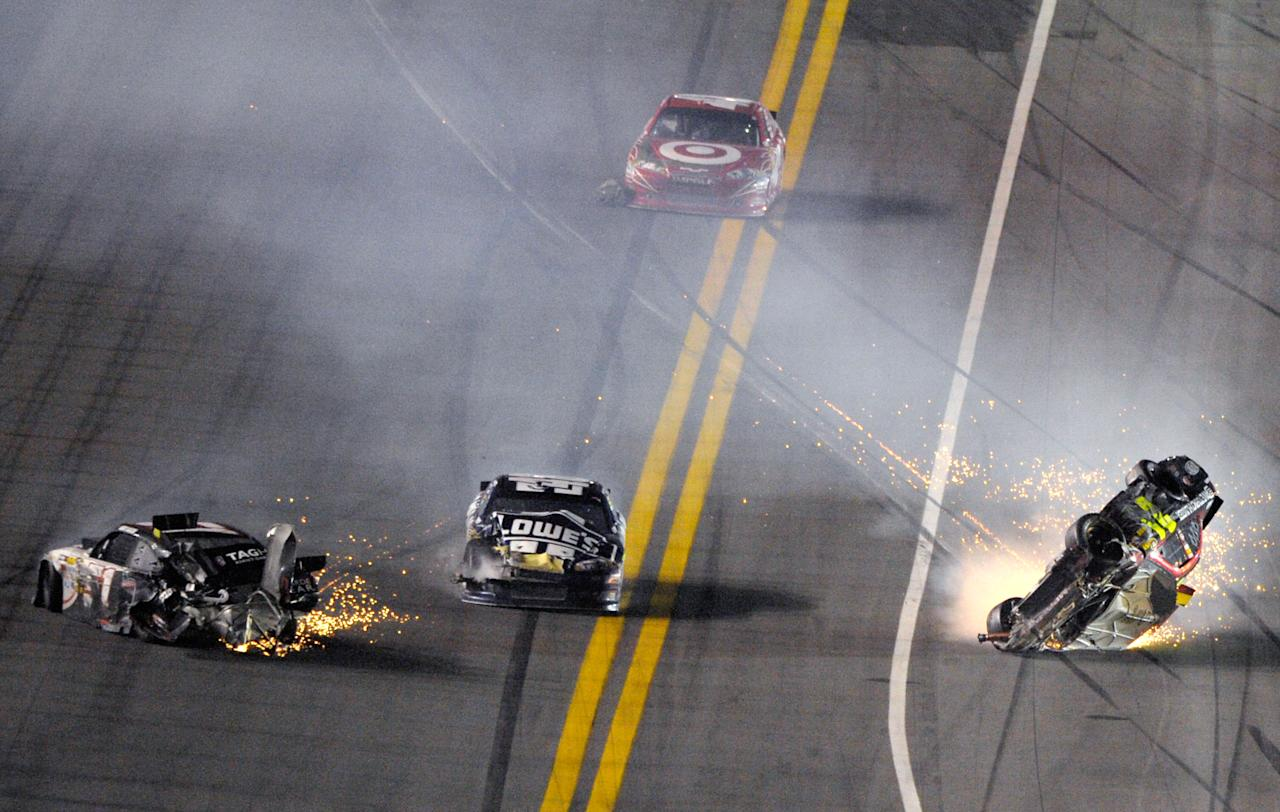 Jeff Gordon's car, right, rolls after a collision with Kurt Busch, left, as Jimmie Johnson, center, drives past in his damaged car during the NASCAR Budweiser Shootout auto race at Daytona International Speedway, Saturday, Feb. 18, 2012, in Daytona Beach, Fla. (AP Photo/Phelan M. Ebenhack)