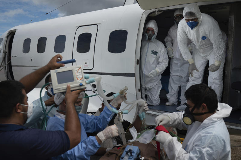 Health workers prepare to move 89-year-old COVID-19 patient Sildomar Castelo Branco into an aircraft as he is transferred from Santo Antonio do Içá to a hospital in Manaus, Brazil, Tuesday, May 19, 2020. (AP Photo/Felipe Dana)
