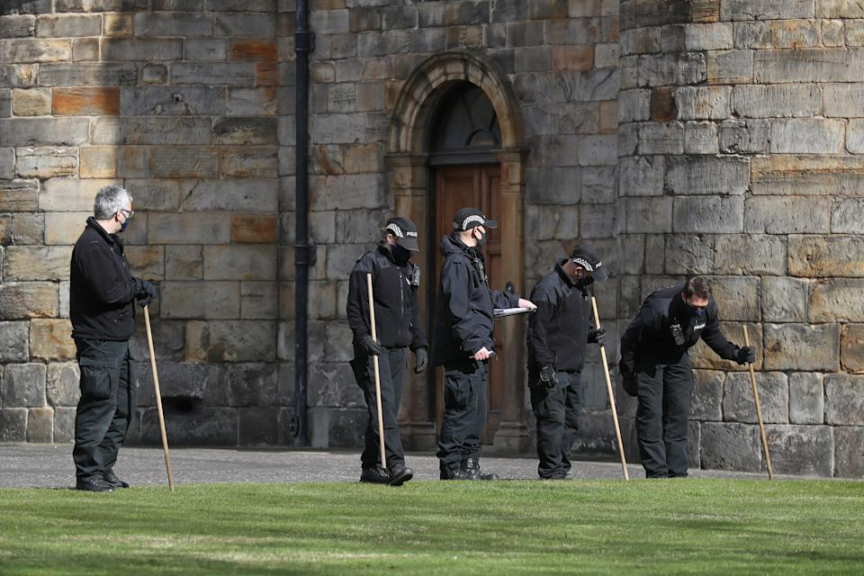 Police officers conduct a search within the grounds of the Palace of Holyroodhouse in Edinburgh. (PA Images)