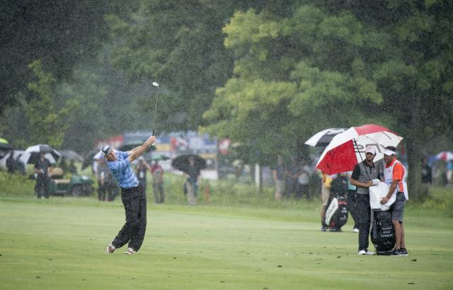 Jim Furyk hits on the 15th fairway during a downpour in the final round of the Canadian Open golf tournament, Sunday, July 27, 2014, in Montreal. (AP Photo/The Canadian Press, Paul Chiasson)