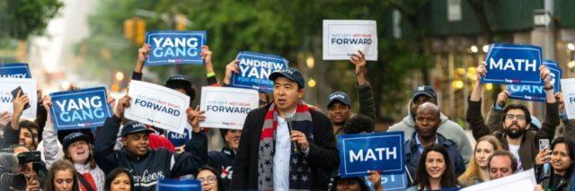 Andrew Yang surrounded by supporters at a rally.